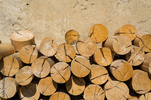 Fotografía  Pile of worked wooden roundish clear beautiful logs, stacked firewood background