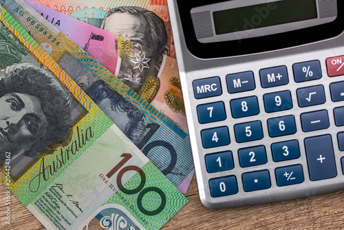 Australian Dollar Banknotes With Calculator On Wooden Table