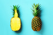 Leinwanddruck Bild - Whole pineapple and half sliced fruit on blue background. Top View. Copy Space. Bright pineapples pattern for minimal style. Pop art design, creative concept