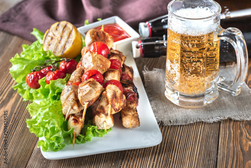 Grilled chicken skewers with mug of beer