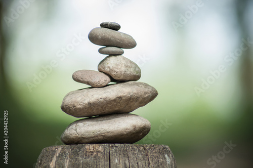 Fotografía  closeup of stones balance on wooden fence on green blurred background
