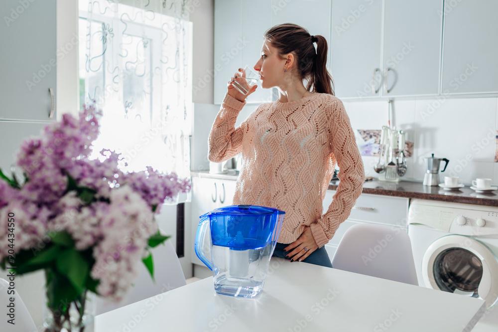 Fototapeta Woman drinking filtered water from filter jug in kitchen. Modern kitchen design. Healthy lifestyle