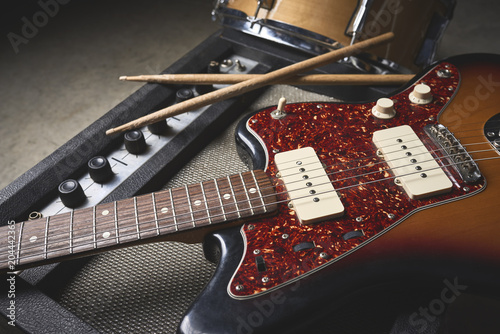 Photo a group of musical instruments including an electric guitar, drum, cymbal, and a