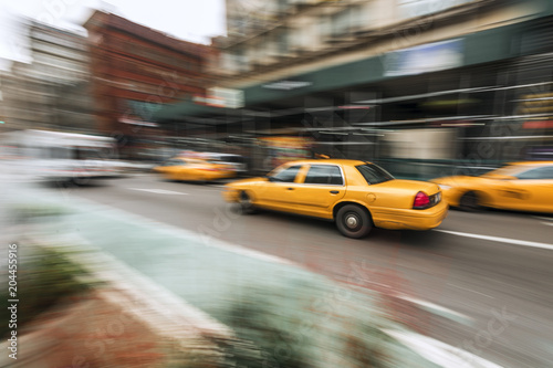 Staande foto New York TAXI A traditional NYC taxicab drives down a Manhattan street with motion blur captured with slow shutter speed directly in image