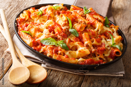 Fototapeta Casserole ziti pasta with minced meat, tomatoes, herbs and cheese close-up on a plate. horizontal obraz