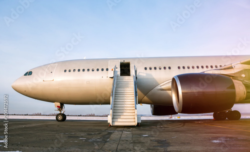 Obraz Wide body passenger airplane with a boarding stairs at the airport apron in the evening sun - fototapety do salonu