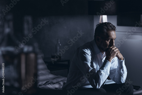 Portrait of a lonely mature man with depression sitting on a bed in a gray room Canvas Print