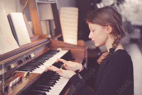 Fotografiet  Young girl playing organ