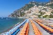 View of famous rows of blue and orange beach umbrellas on Positano Beach, Amalfi Coast, Italy.