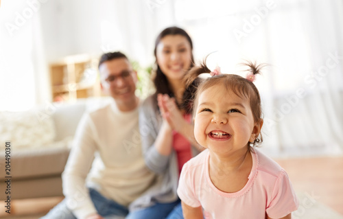 Photo  family and people concept - happy little daughter with mother and father at home
