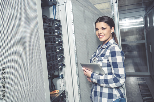 Fotografia Woman technician working on and inspecting servers in server room