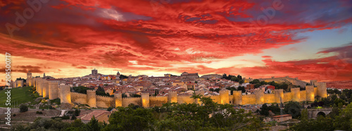 Walls of Medieval city of Avila at sunset with lights on, Spain
