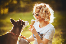 Girl In Glasses With Ice Cream In Her Hands Is Smiling At Her Pet In The Summer In The Park
