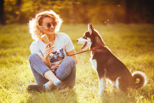 A Girl In Jeans And In White T-shirt With Ice Cream In Her Hand Sits Cross-legged In The Meadow And Looks At A Pet In The Park In The Summer