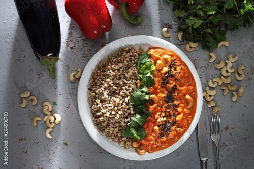 Czerwone curry. Danie obiadowe. Kolorowe warzywa w sosie podane z kaszą i ziolami