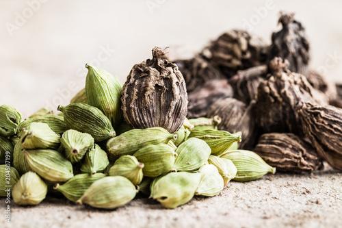 Fototapeta Black and green cardamom whole seeds on wooden background. obraz