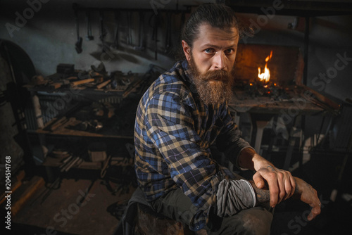 Foto Portrait of a real Brutal blacksmith of a man with a beard after working in his workshop against the background of a burning flame