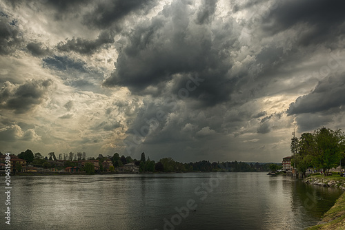 Keuken foto achterwand Onweer Storm clouds over the Ticino river in spring season