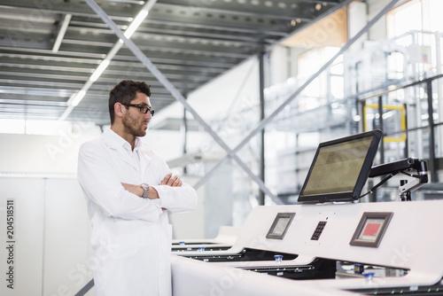 Man wearing work coat looking at screen in factory