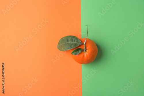 Single Bright Ripe Tangerine on Duotone Green Orange Background. Styled Creative Image. Citrus Fruit Vitamins Summer Vegan Fashion Concept. Food Poster with Copy Space