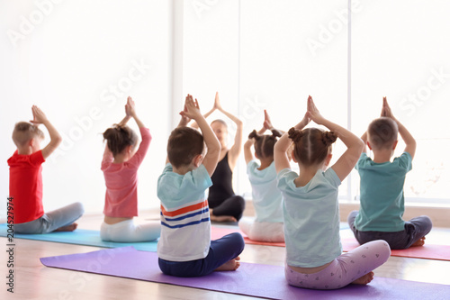 Tuinposter Ontspanning Little children and their teacher practicing yoga in gym