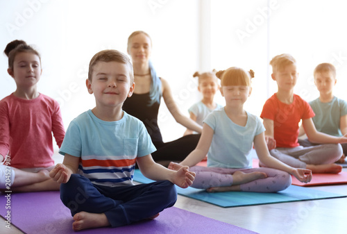 Obraz Little children and their teacher practicing yoga in gym - fototapety do salonu