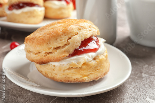 Fototapeta Tasty scone with clotted cream and jam on plate, closeup