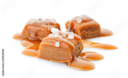 Fotografia  Delicious candies with caramel sauce and salt on white background