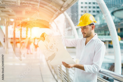 Engineer man wearing safety helmet and hold blueprint document at engineer man wearing safety helmet and hold blueprint document at construction site concept of project malvernweather Choice Image