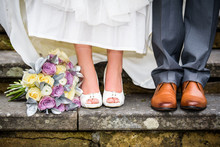 Closeup Of Bride And Groom Feet And Wedding Bouquet Of Flowers