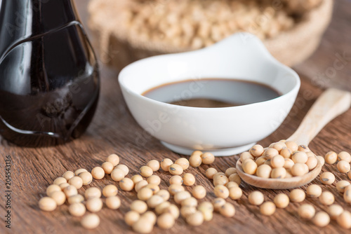 Soy sauce in bowl with bottle and soy bean on wood table.