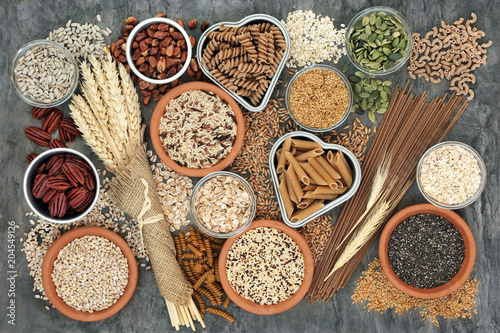 Keuken foto achterwand Assortiment High fibre healthy food concept with fresh whole wheat pasta, cereals, grains, seeds, nuts and wheat sheaths. Foods high in omega 3, antioxidants and vitamins. Rustic background on marble, top view.