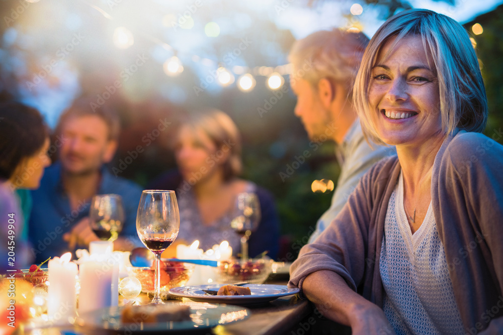 Fototapety, obrazy: Group of friends gathered around a table in a garden on a summer evening to share a meal and have a good time together. Focus on a beautiful woman