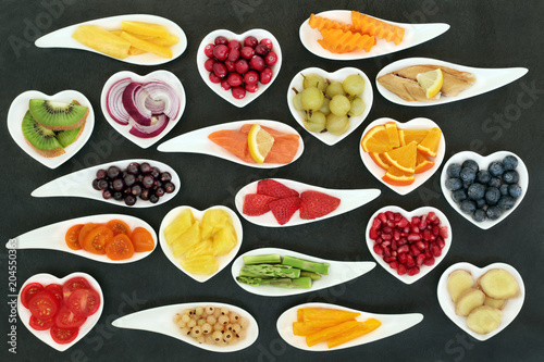 Poster Assortiment Health super food nutrition for a healthy heart with fresh fruit, vegetables and fish with foods high in omega 3 fatty acids, antioxidants, anthocyanins, fibre and vitamins. On slate top view.