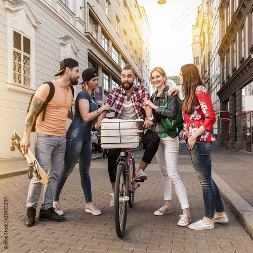 slightly drunken hipster man on a pink bicycle gets support of his friends. cheerful people in the city having fun in the streets