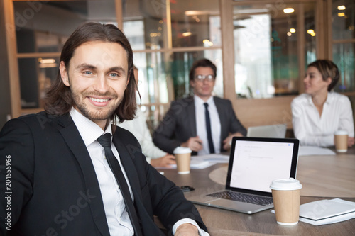 Fototapety, obrazy: Smiling handsome young businessman in suit and tie looking at camera posing at group meeting with partners, happy executive manager, successful team leader or professional business coach portrait