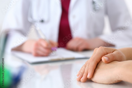 Fototapety, obrazy: Female doctor filling up  an application form while consulting patient. Just hands. Medicine and health care concept