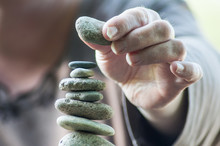 Closeup Of Hand Of Woman Making Stones Balance On Wooden Table On Green Blurred Background