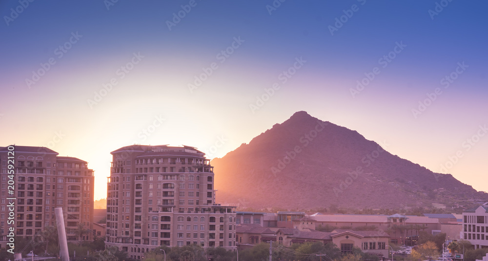 Sun setting over Scottsdale, Arizona waterfront area with Camelback Mountain glowing.