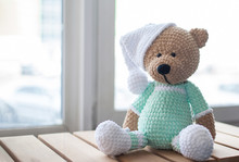 Brown Stuffed Animal Teddy Bear In Mint-colored Clothes And White Hat On The Wood.