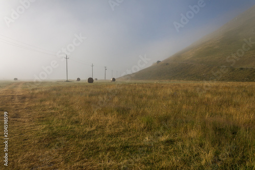 Keuken foto achterwand Crimson View of Castelluccio di Norcia (Umbria, Italy) upland at morning, with power lines and mist