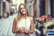Leinwanddruck Bild - Beautiful young blonde woman smiling in urban background.