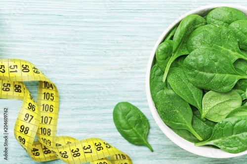 Tape measure and spinach leaves in bowl top view. Diet and healthy food concept.