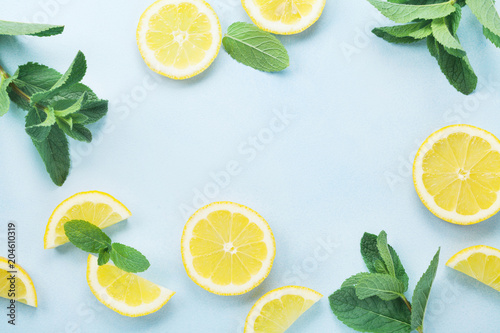Lemon slices and mint leaves on blue pastel table top view. Ingredients for summer lemonade and cocktail. Flat lay style.