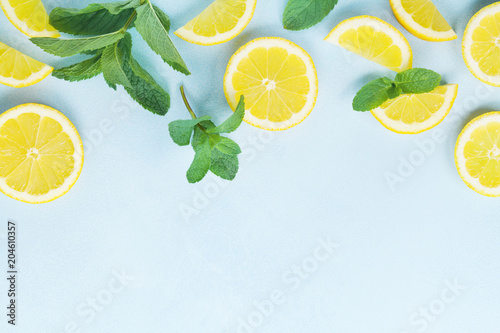 Juicy lemon slices and mint leaves on blue table top view. Flat lay style.