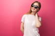 canvas print picture - Beautiful young blonde girl in glasses standing on pink background wearing jeans, pink top smiling snow white smile, wearing black glasses and looking perfect promotional photo