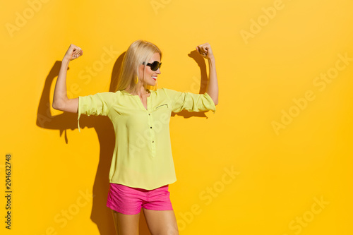 Fotografia  Beautiful Vibrant Woman Is Flexing Muscles, Smiling And Looking Away