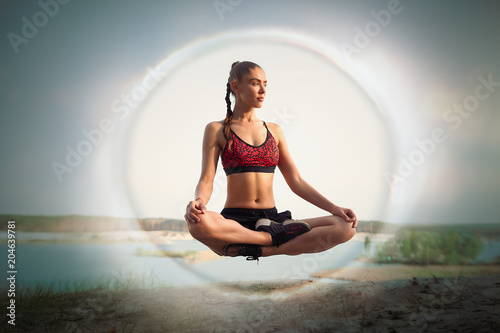 beautiful young girl sportswoman levitates in lotus position on nature near lake