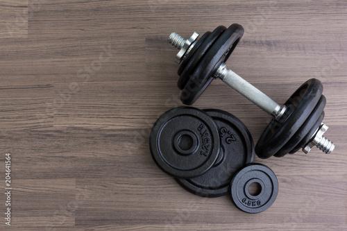black dumbbell on wooden floor in top view Fototapeta