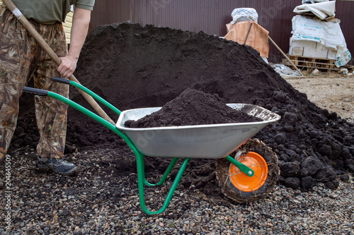 Canvas Print farmer loaded black soil in the wheelbarrow